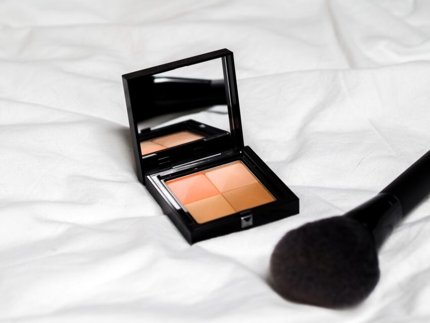 black and brown makeup palette on white textile